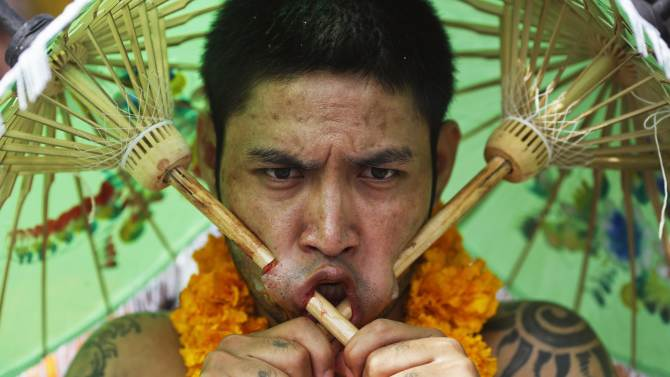 A devotee of the Chinese Jui Tui Shrine with two umbrellas pieced through his cheeks walks during a procession celebrating the annual vegetarian festival in Phuket
