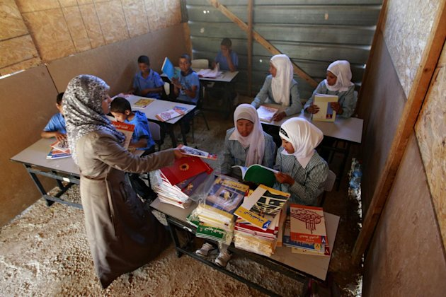 Palestinian Bedouin Students attend class at their school at Khan al-Ahmar, near the west bank city of Jericho, Sunday, Sept 2. 2012. Dozens of Palestinian children in the ramshackle Bedouin community outside Jerusalem defy Israeli authorities with a simple act: going to school for the beginning of the scholastic year. Their school is a series of buildings made of mud and old tires that were built over the objections of Israeli authorities who are now threatening to demolish the structures. Israeli authorities say the community is willfully building illegally. (AP Photo/Majdi Mohammed)