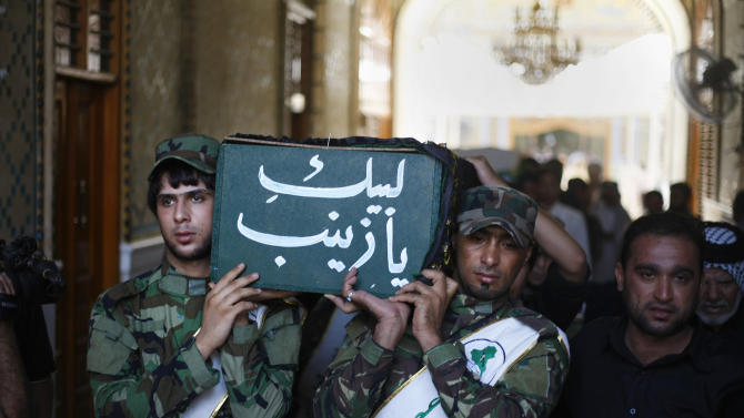 Members of Iraq's Hezbollah Brigades carry the coffin of a Shiite fighter, Methaq Najm Abdullah, during a funeral procession in the Shiite holy city of Najaf, 100 miles (160 kilometers) south of Baghdad, Iraq, Thursday, Aug. 22, 2013. Three Iraqi Shiite fighters were killed in Syria a few days ago, Iraq Hezbollah Brigades officials said on Thursday. (AP Photo)