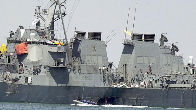 FILE - In this Oct. 15, 2000 file photo, investigators in a speed boat examine the hull of the USS Cole at the Yemeni port of Aden, after a powerful explosion  ripped a hole in the U.S Navy destroyer, killing at least 17 sailors and injuring some 30 others. Abd al-Rahim al-Nashiri, a Saudi national accused in the 2000 bombing of the USS Cole warship, faces trial in a special tribunal for war-time offenses known as a military commission for allegedly orchestrating the bombing of the USS Cole as well as attacks on two other ships. But his lawyers say that since the U.S. wasn't at war at that time, the 47-year-old shouldn't be tried at Guantanamo. (AP Photo/Dimitri Messinis, file)