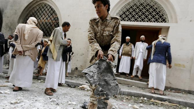 Houthi militant collects evidence at site of car bomb attack near Ismaili mosque in Yemen's capital Sanaa
