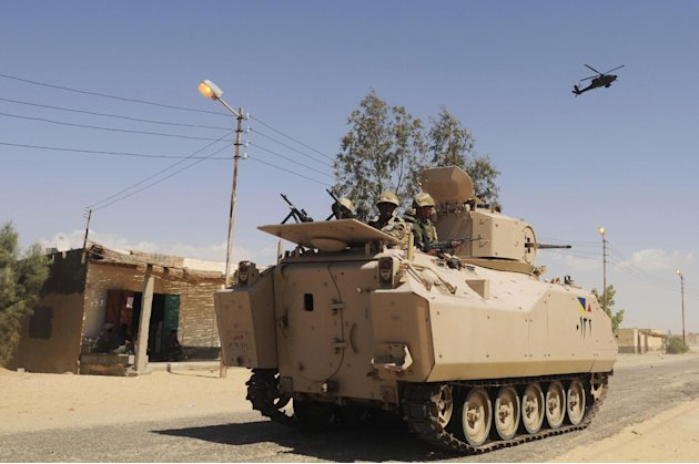 Egyptian Army soldiers patrol in an armored vehicle backed by a helicopter gunship during a sweep through villages in in Sheikh Zuweyid, northern Sinai, Egypt, Tuesday, May 21, 2013. Egypt's governmen