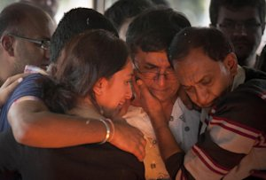 Ramesh Vaya, center, is comforted by family members …