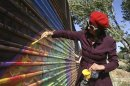 Artist Gretchen Baer paints on a fence marking the U.S. border in Naco