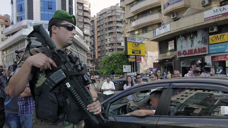 A Lebanese army soldier stands at one of their checkpoints in a southern suburb of Beirut, Lebanon, Monday, Sept. 23, 2013. Hundreds of soldiers and policemen will deploy in strongholds of the militant Hezbollah group south of Beirut. (AP Photo/Bilal Hussein)