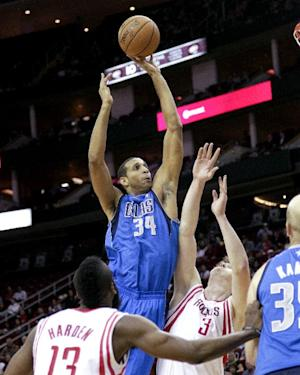 Dallas Mavericks' Brandan Wright (34) shoots over Houston Rockets' Omer Asik (3) during the first half of an NBA basketball game, Saturday, Dec. 8,  2012, in Houston. (AP Photo/Bob Levey)