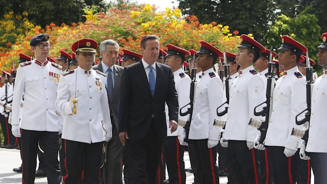 Britain's PM David Cameron inspects an honour guard with Singaporean counterpart Lee Hsien Loong during a welcome ceremony at the Istana in Singapore
