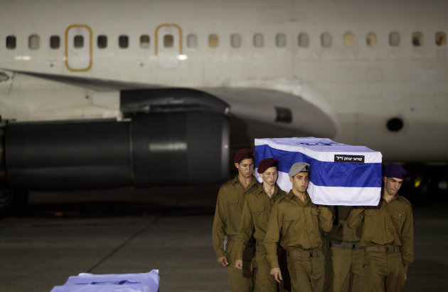 Israeli soldiers carry a coffin of victimes killed in bombing in Bulgaria after the remains arrived at Tel Aviv airport, Israel, Friday, July, 20, 2012. A man carried out a deadly suicide attack on a 