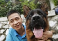 Dog dealer Nguyen Duy Hiep poses with his German shepherd Largo by a lake in Hanoi September 24, 2013. Times in Vietnam are changing, where a love for dogs goes beyond the soups and barbecues that have earned the country an unsavoury reputation as the global hub of canine cuisine. REUTERS/Kham
