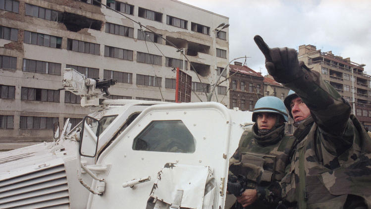 FILE In this  Dec. 1, 1994 file photo French U.N. soldiers point to an area from which four anti-tank missiles were fired, in Sarajevo, Bosnia. With the U.N. unable to agree how to protect civilians against Bashar Assad's forces, Western officials are discussing creation of safe corridors to deliver aid to Syrians trapped by the crackdown.  Similar measures failed badly during the war in Bosnia two decades ago that killed over 100,000 people and left millions homeless. The lesson of Bosnia is that without all sides honoring the agreement _ and without a robust military response in case they don't _ such measures may have little effect and could actually prolong the misery.  (AP Photo/Enric F. Marti, file)