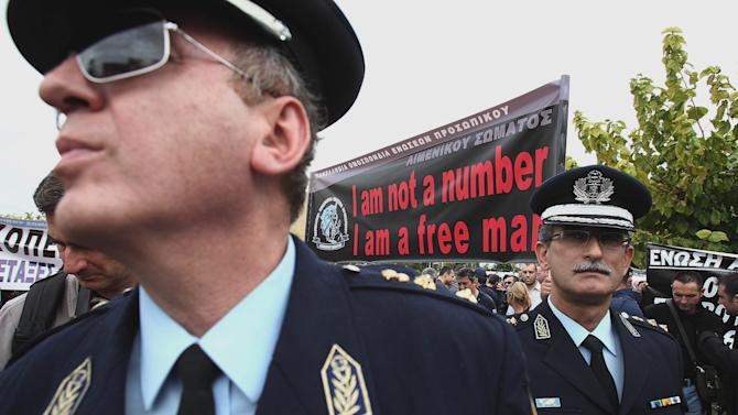 Police officers stand in front of a banner during a protest in central Athens on Thursday, Nov. 1, 2012. More than a thousand protesting officers from the police, coast guard and fire department joined a rally in Athens to demonstrate against government cuts, in the latest protest ahead of a planned two-day general strike next week.  (AP Photo/Thanassis Stavrakis)