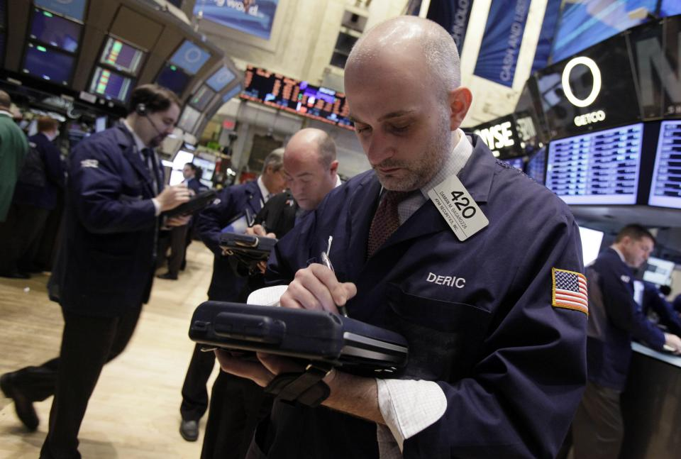 Damian Bagarozza, right, works with fellow traders on the floor of the New York Stock Exchange Monday, March 19, 2012.  Wall Street was poised for a lower opening Tuesday March 20, 2012 with Dow futures and the broader S&P 500 futures 0.5 percent lower.  (AP Photo/Richard Drew)