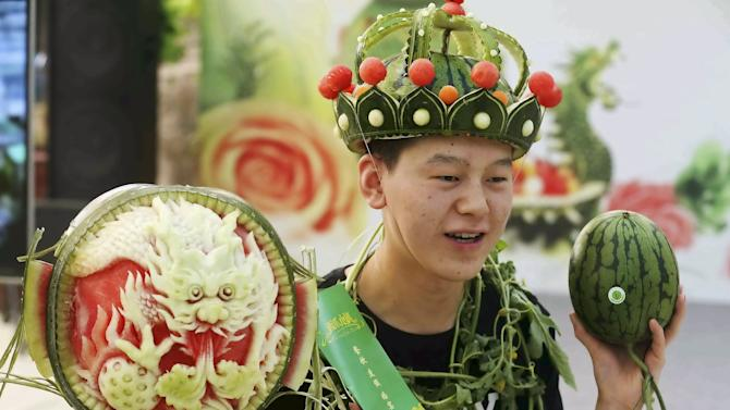 A man wearing a headpiece made of watermelon peel stands next to a watermelon sculpture during an annual watermelon festival in Daxing