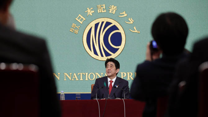 """Japanese Prime Minister Shinzo Abe, center, speaks during a press conference at the Japan National Press Club in Tokyo, Friday, April 19, 2013. Abe said reviving Japan's growth will depend on further opening the economy and tapping the underutilized potential of its women and advanced technology. Abe outlined the next steps of his grand plan for restoring Japan's economic power Friday, describing a slew of initiatives he said would help awaken Japan's """"sleeping dynamism."""" (AP Photo/Shizuo Kambayashi)"""