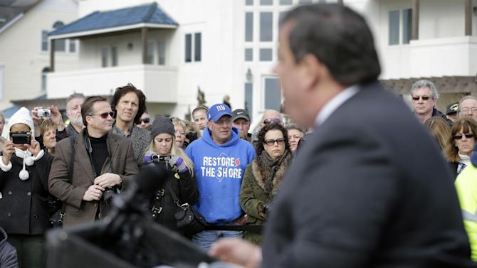 Bill Pahlck wears a Restore The Shore sweatshirt Wednesday, Jan. 9, 2013, in Belmar, N.J., as he and others listen to Gov. Chris Christie describe rebuildng plans as Belmar began construction on a 1.3-mile boardwalk to replace the walkway destroyed by Superstorm Sandy in October. Christie helped Belmar officials kick off the construction Wednesday morning. (AP Photo/Mel Evans)