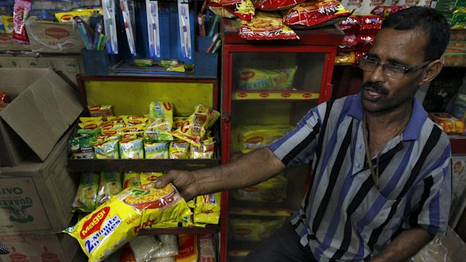 A vendor sells a Maggi noodles packet to a customer  inside a grocery shop in Kolkata