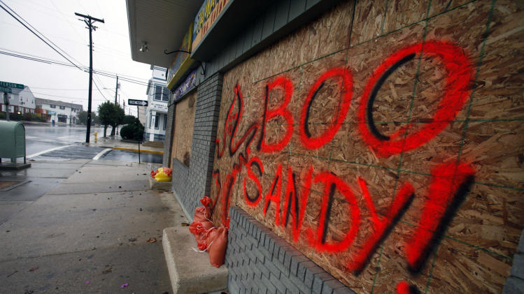 "Windows on a store front are boarded up in Margate N.J., with the message ""Boo Sandy!"", as the area prepares for the arrival of the Superstorm, Sunday, Oct. 28, 2012. (AP Photo/Joseph Kaczmarek)"