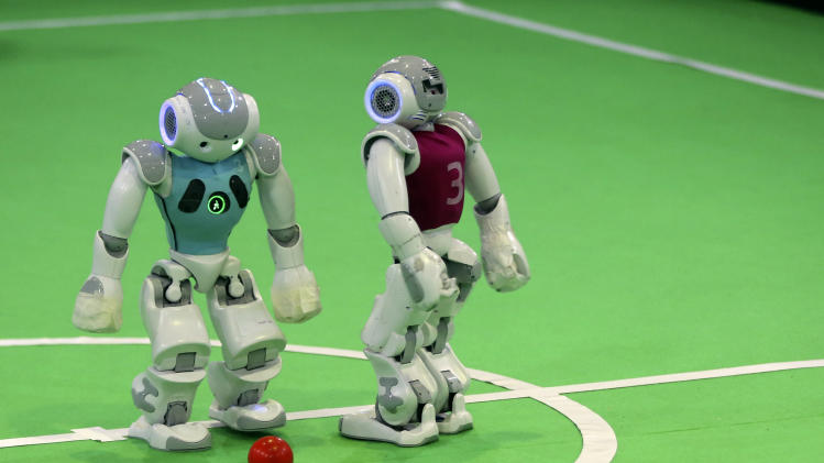 In this Thursday, April 10, 2014 photo, humanoid robots play during a soccer match during the international robotics competition, RoboCup Iran Open 2014, in Tehran, Iran. Students from 22 countries including Britain, France, Portugal, Italy, Germany, Sweden, Netherlands, Brazil, Mexico, Japan, China, Thailand, India, Pakistan, UAE, Canada, Turkey, Colombia, Egypt and Indonesia were competing during the three-day event. (AP Photo/Vahid Salemi)
