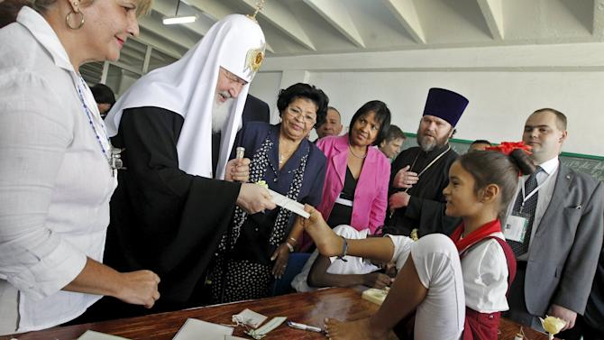 "Patriarch Kirill, the head of the Russian Orthodox Church, receives a message written on a paper from a child at the special needs school ""Solidaridad con Panama"" (Solidarity with Panama) in Havana"