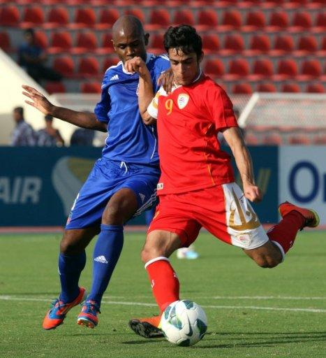 Abdulaziz al-Miqbali (right) outsmarts Haiti's Frantz Bertin in a friendly in Muscat, on March 20, 2013