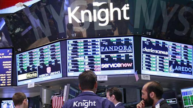 Traders work at the Knight Capital kiosk on the floor of the New York Stock Exchange