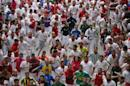 Revelers are chased by a Fuente Ymbro ranch fighting bull during the running of the bulls of the San Fermin festival, in Pamplona, Spain, Saturday, July 12, 2014. Revelers from around the world arrive in Pamplona every year to take part on some of the eight days of the running of the bulls. (AP Photo/Daniel Ochoa de Olza)