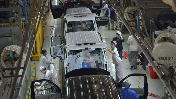 Employees work inside a factory manufacturing automobiles in Shenyang