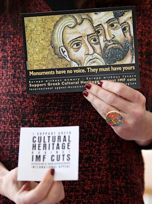 A Greek archaeologist union leader holds flyers against the impact of  austerity measures on the country's rich cultural heritage  during a press conference in Athens, Wednesday, March 14, 2012. Union representatives said illegal excavations have increased, and claimed that despite two high-profile thefts from Greek museums the government is planning to reduce spending on museum security. (AP Photo/Thanassis Stavrakis)
