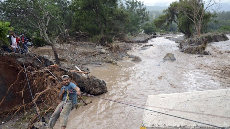 A man uses a makeshift zip line to cross a river after a bridge collapsed under the force of the rains caused by Tropical Storm Manuel near the town of Petaquillas, Mexico, Wednesday, Sept. 18, 2013. The death toll from devastating twin storms climbed to 80 on Wednesday as isolated areas reported to the outside world. Mexican officials said that a massive landslide in the mountains north of Acapulco could drive the number of confirmed dead even higher. (AP Photo/Alejandrino Gonzalez)