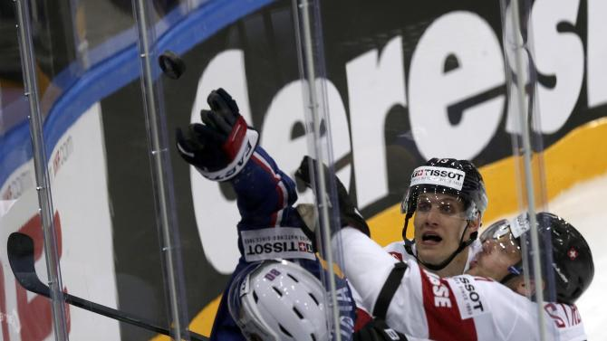 France's Da Costa tries to catch the puck next to Switzerland's Streit and du Bois during their Ice Hockey World Championship game at the O2 arena in Prague