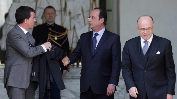 French President Hollande walks with Prime Minister Valls and Interior Minister Cazeneuve following the weekly cabinet meeting at the Elysee Palace in Paris