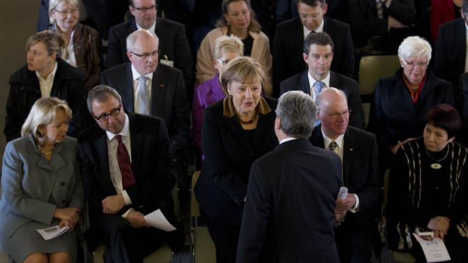 German Chancellor Angela Merkel, center, welcomes presidential candidate Joachim Gauck at an ecumenical service prior to Germany's Federal Assembly in Berlin, Sunday, March 18, 2012. The assembly convened solely for the purpose to elect the German President. (AP Photo/Markus Schreiber, Pool)