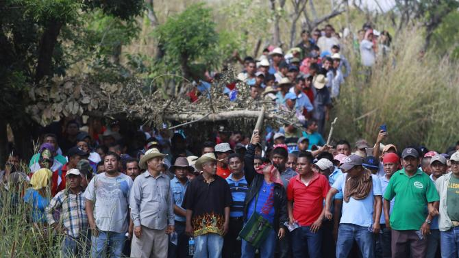 People stand in front of a military checkpoint during a demonstration to demand the checkpoint's  withdrawal in Ayutla