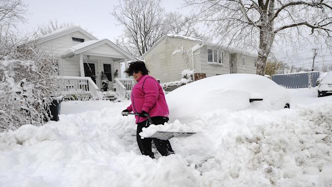 April Palmieri digs out her car in front of her home, background left, on 17th Street after a snow storm on Saturday, Feb. 9, 2013 in Bayville, N.Y. Palmieri had five feet of water in her basement as result of the rains from Superstorm Sandy. A howling storm across the Northeast left the New York-to-Boston corridor shrouded in 1 to 3 feet of snow Saturday, stranding motorists on highways overnight and piling up drifts so high that some homeowners couldn't get their doors open. More than 650,000 homes and businesses were left without electricity. (AP Photo/Kathy Kmonicek)