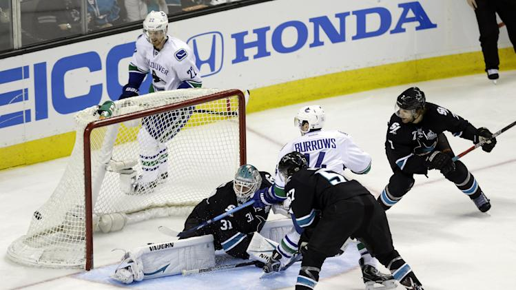 Vancouver Canucks center Alex Burrows (14) scores past San Jose Sharks goalie Antti Niemi, of Finland, during the third period of Game 4 of their first-round NHL hockey Stanley Cup playoff series in San Jose, Calif., Tuesday, May 7, 2013. (AP Photo/Marcio Jose Sanchez)