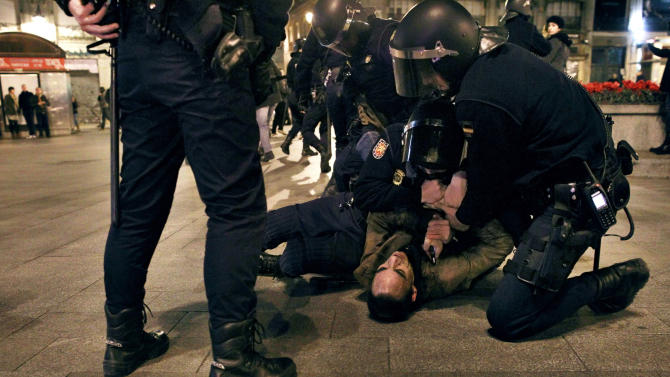 Riot police detain a protestor during a demonstration against corruption in Madrid, Spain, Saturday, Feb. 2, 2013. Riot police clashed with protesters in Madrid late Saturday and impromptu demonstrations broke out in several other Spanish cities following the prime minister's televised denial that he had accepted under-the-table payments.  (AP Photo/Andres Kudacki)