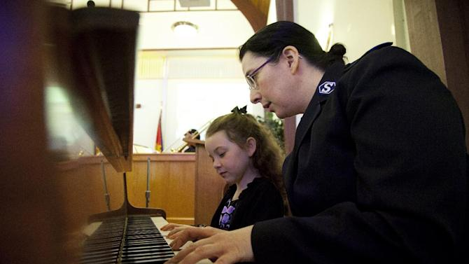 Piano teacher Maria Mathieson practices a duet with Jubilee Delaney, 6, before the Alexandria School for the Performing Arts winter recital in the chapel of the Salvation Army, Sunday, March 11, 2012, in Alexandria, Va. A survey of Salvation Army youth programs in more than 80 cities shows more than eight in 10 programs saw increased demand from children and families in the past year as the nation's high jobless rate and cutbacks in government and private funding strained charities. The survey released to The Associated Press found 56 percent of the charity's youth programs _ including camps, preschools, daycare and after-school programs _ are operating at or beyond their capacity.(AP Photo/Carolyn Kaster)