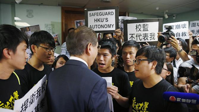 """In this July 28, 2015 photo, university students hold placards in front of Arthur Li, one of the school leaders, outside a conference room where school leaders were deliberating in the University of Hong Kong. Students at Hong Kong's most prestigious university say its academic freedom is under attack in what they maintain is the politically motivated stalling of the appointment of an administrator who supported last year's pro-democracy protests. A banner, front right, reads """"Chancellor is not representing me."""" (AP Photo/Kin Cheung)"""