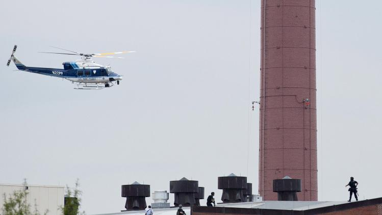 A police helicopter is seen as police walk on the roof of a building as they respond to a shooting at the Washington Navy Yard, in Washington