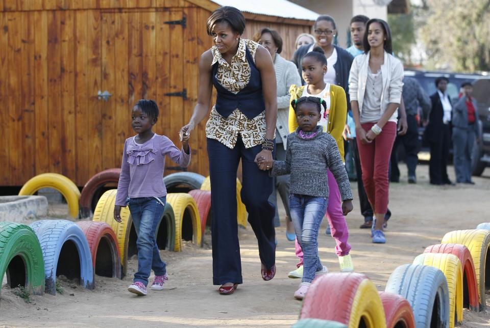 First lady Michelle Obama walks with children as she visits the Emthonjeni Community Center in Zandspruit Township, Johannesburg, South Africa, Tuesday, June 21, 2011. Also seen at rear are daughters Sasha and Malia Obama, mother Marian Robinson, niece Leslie Robinson and nephew Avery Robinson. (AP Photo/Charles Dharapak, Pool)