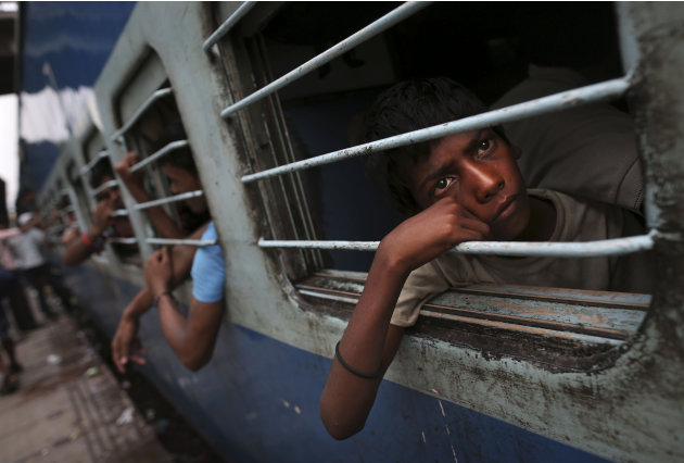 A young Indian boy watches from a window of a stalled train as he waits for the train to resume its services following a power outage at a railway station in New Delhi, India, Tuesday, July 31, 2012. 