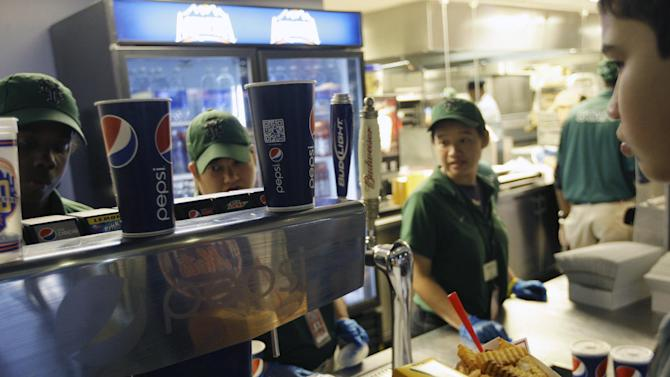 Emilio Cordova, right, chooses a soft drink during a baseball game between the New York Mets and the Washington Nationals Wednesday, Sept. 12, 2012, in New York. Health officials are expected to approve an unprecedented 16-ounce limit on sodas and other sugary drinks sold at restaurants, delis and movie theaters. (AP Photo/Frank Franklin II)