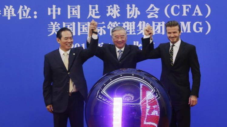David Beckham, Hu Qili and Cai Zhenhua raise their hands during a ceremony at the Great Hall of the People in Beijing