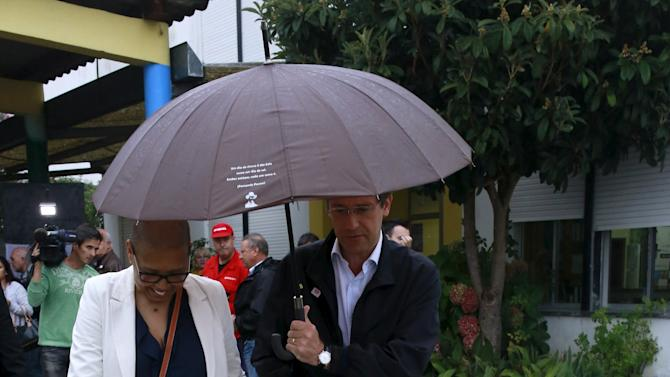 Portugal's Prime Minister and Social Democratic party leader Pedro Passos Coelho leaves a polling station with his wife after voting during the general election in Massama