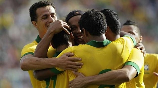 Brazil's Ronaldinho (C) congratulates Neymar (2L) as teammates embrace him after scoring a goal against Bolivia during a international friendly match