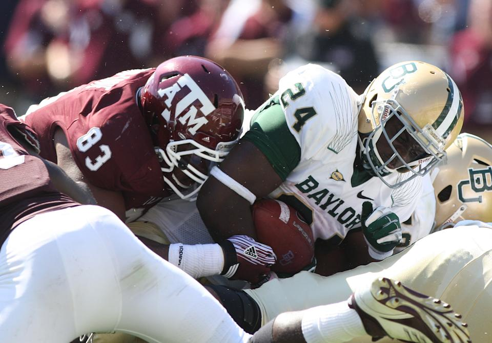 Baylor's Terrance Ganaway (24) gets tackled by Texas A&M's Tony Jerod-Eddie (83) during the first half of an NCAA college football game, Saturday, Oct. 15, 2011, in College Station, Texas. (AP Photo/Jon Eilts)