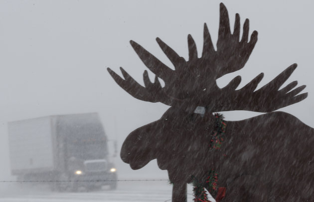 A truck drives in near whiteout conditions past a silhouette of a moose, on Interstate 80 near Gretna, Neb., Thursday, Feb. 21, 2013. Much of the nation's heartland is experiencing heavy snow, treache
