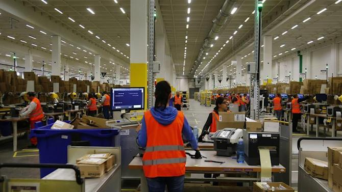 Workers handle items for delivery at Amazon's new distribution center in Brieselang