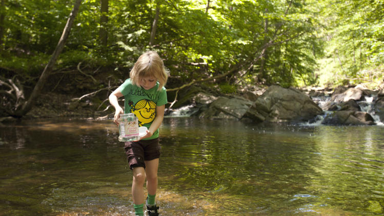 Lori Anne Madison, 6, of Lake Ridge, Va., collects bugs and snails while playing with friends in McLean, Va., on Friday, May 11, 2012. Lori Anne is the youngest contestant in the 2012 National Spelling Bee. (AP Photo/Jacquelyn Martin)