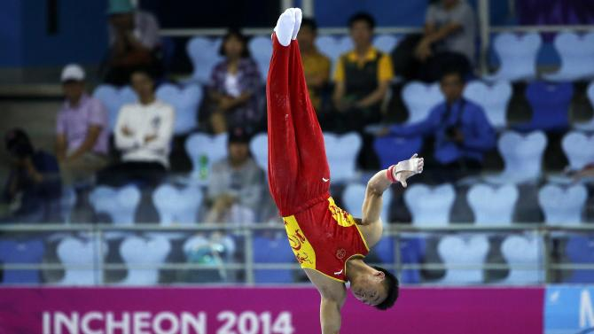 China's Huang Xi competes on the men's horizontal bar in the team gymnastics competition at the Namdong Gymnasium Club during the 17th Asian Games in Incheon